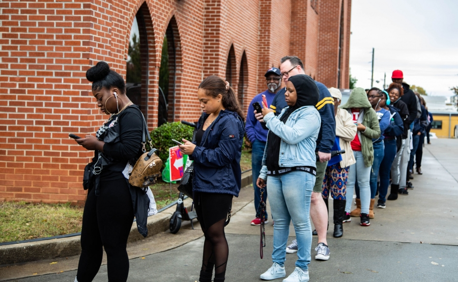 A line of people wraps around a brick building. Most people stand in line, looking at cell phones.