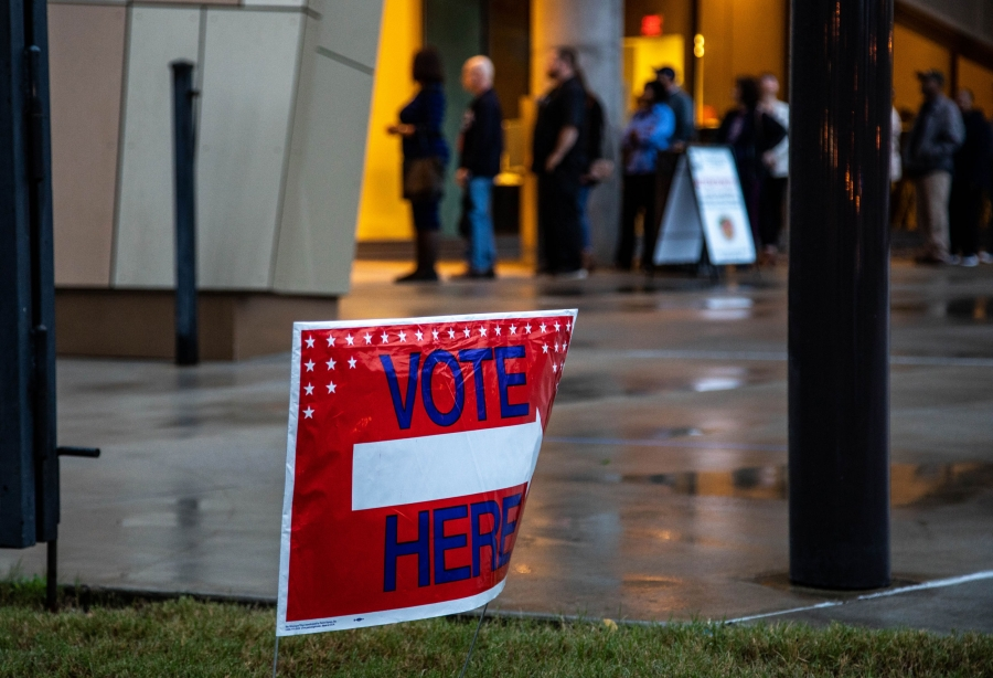 "A red sign says ""Vote here."" In the background, a line of voters extends out the glass doors of a building."