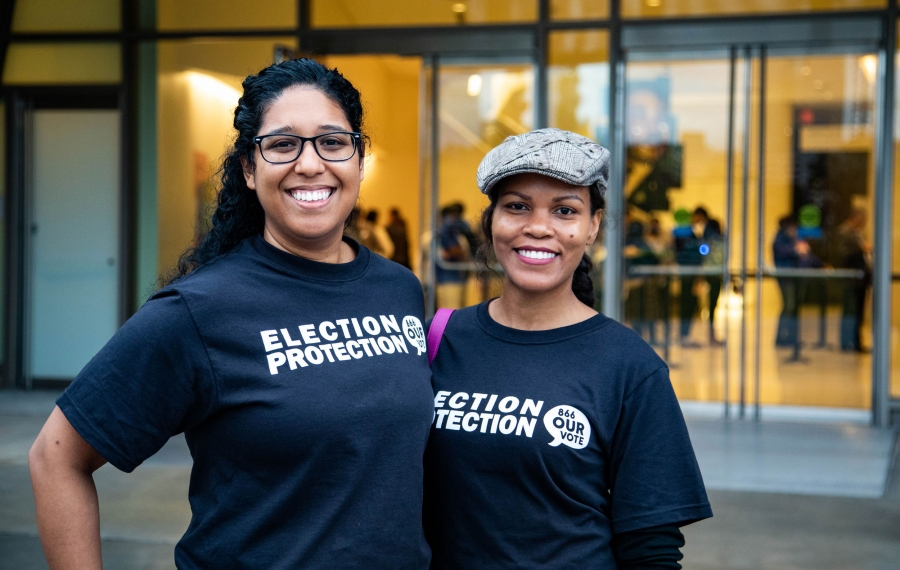 "Two women pose for a photo wearing matching T-shirts which read, ""Election protection."" Behind them, people queue to vote."