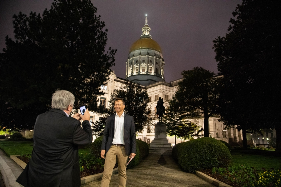 a man in a jackets and slacks get's his photo taken in front of the Georgia state capitol building