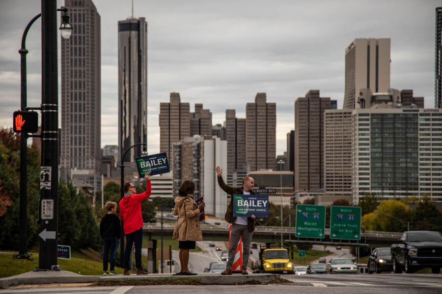 "A group of people hold ""Charlie Bailey for Attorney General"" signs along the side of a road. The Atlanta skyline is behind them."