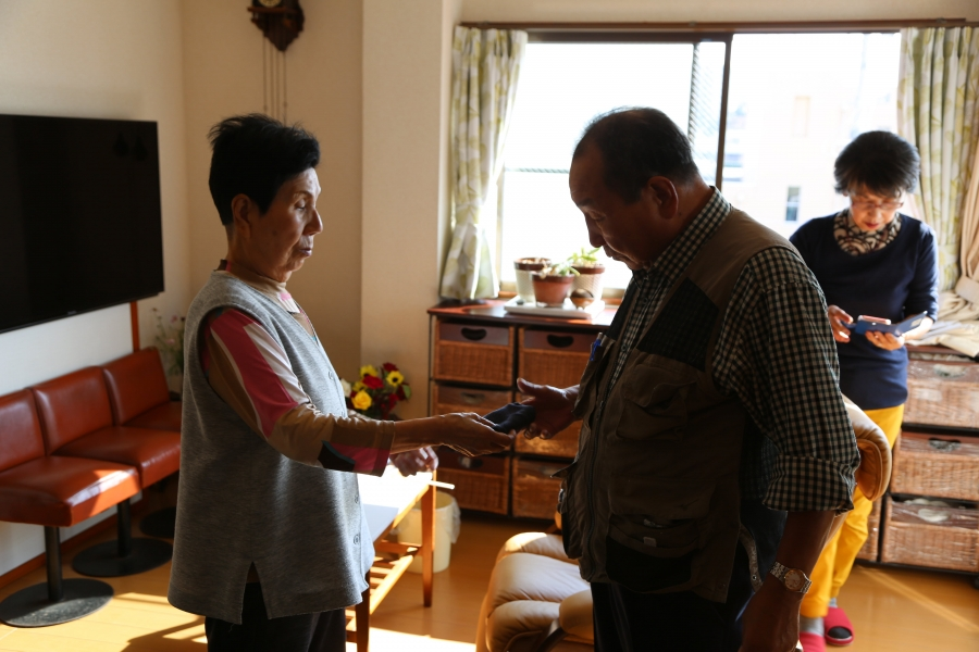 Hideko Hakamada hands her brother Iwao a handkerchief inside her house
