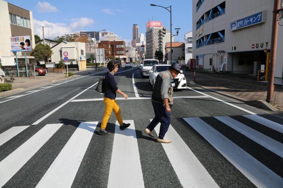 a volunteer follows Iwao Hakamada as he walks across the street