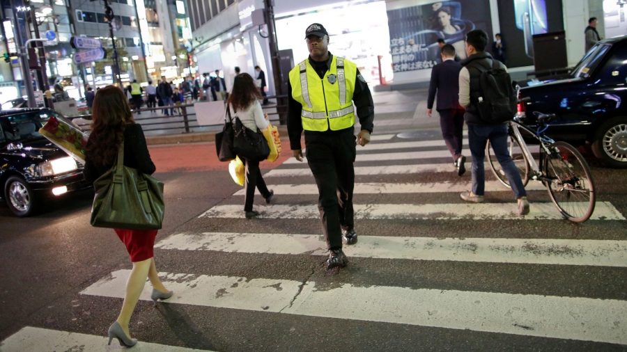 Antonio Nathaniel King, from the US, is shown wearing his security uniform walking across a street in Tokyo.