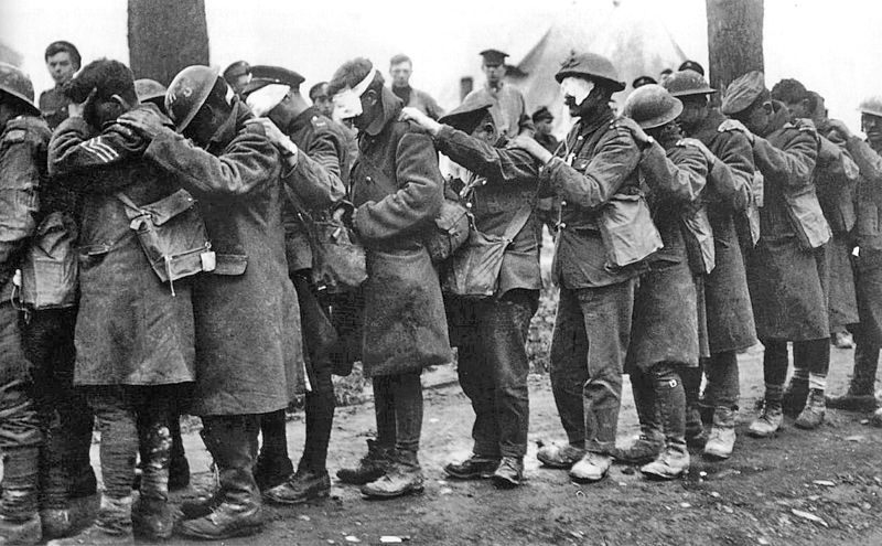 Blinded by German tear gas, blindfolded British soldiers stand in single-file line waiting for treatment.