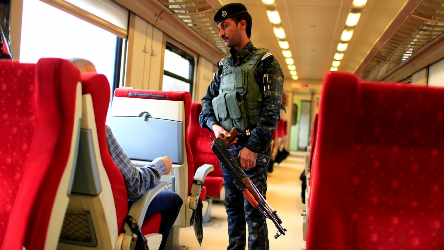 AnIraqi policeman stands guard in a passenger cabin with red seats on the way to Fallujah.