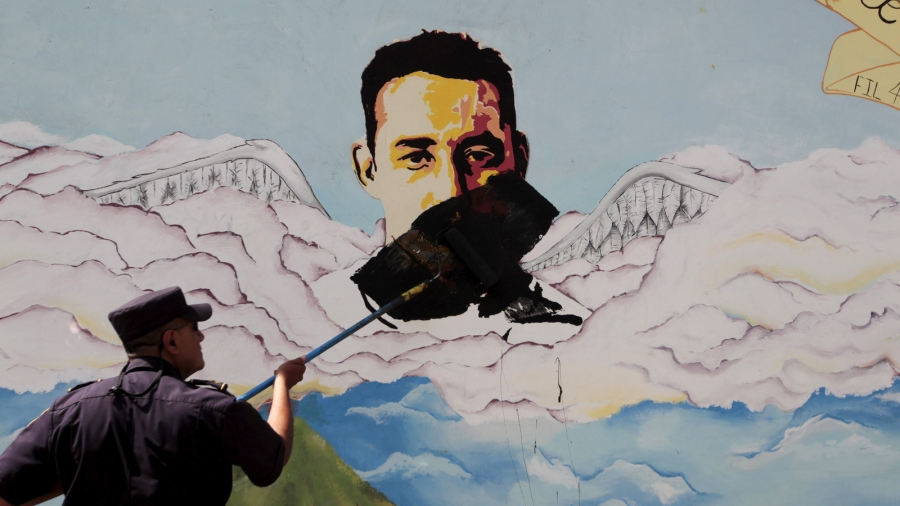 A man paints over graffiti of a face associated with a gang.