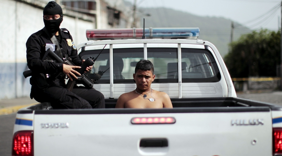 Policewoman in black mask with gun detains shirtless youth sitting in back of police pick-up truck.