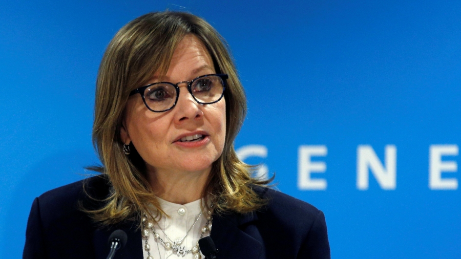 General Motors CEO Mary Barra at a press conference with a blue background.