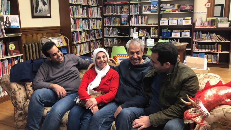 Iranian family reunites on a couch in a library.
