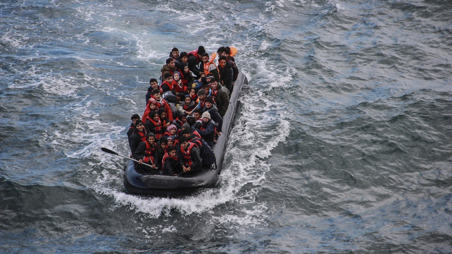 Refugees packed on a boat in the sea.