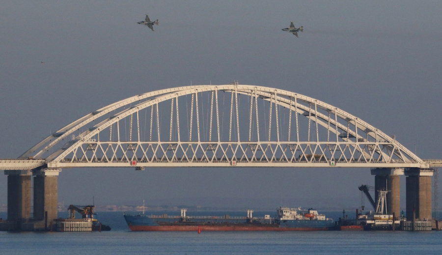 Russian jet fighters fly over a bridge connecting the Russian mainland with the Crimean Peninsula with a cargo ship beneath it
