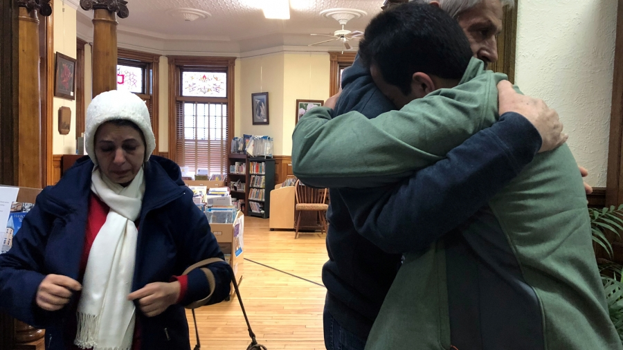 A man embraces his father at a library.