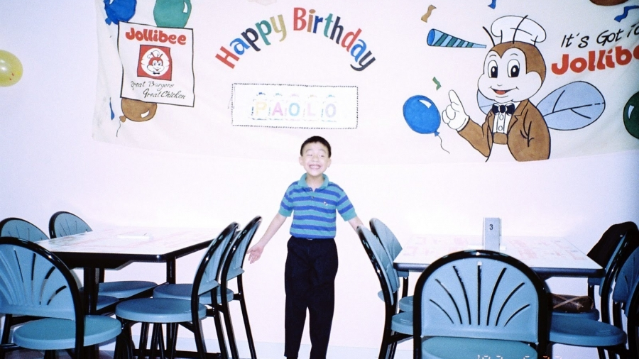 A 7-year-old stands in a Jollibee restaurant with birthday decorations.