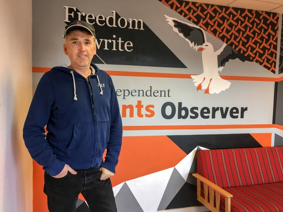 A man stands for a portrait in front of a painted wall that says Barents Observer