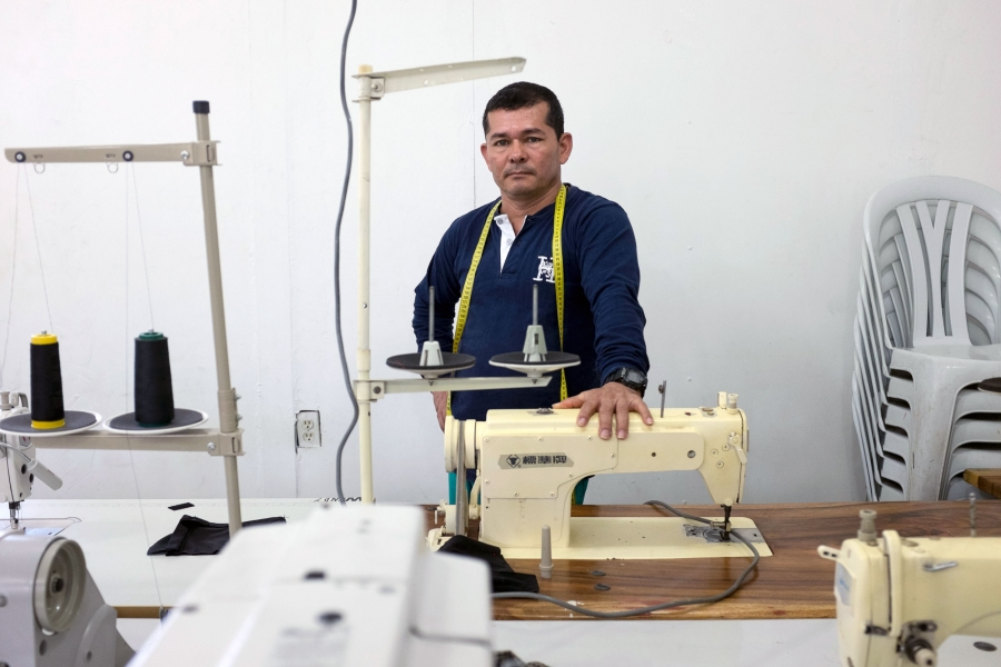 A man poses next to a sewing machine.