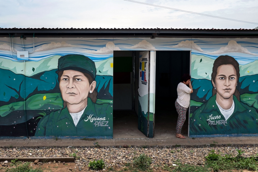 A woman leans in the doorway of a building with images of FARC leaders painted on the outside.