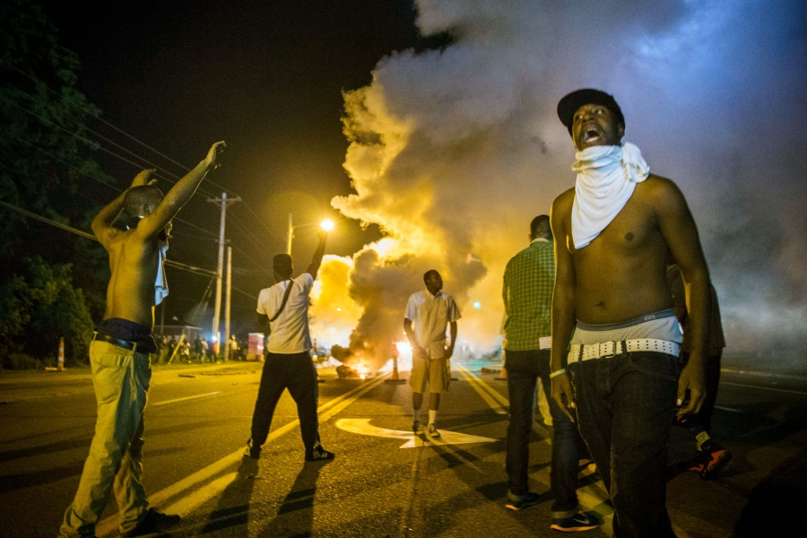 Men stand under the glow of a street light in the street with their hands up. In the distance is a cloud of tear gas.