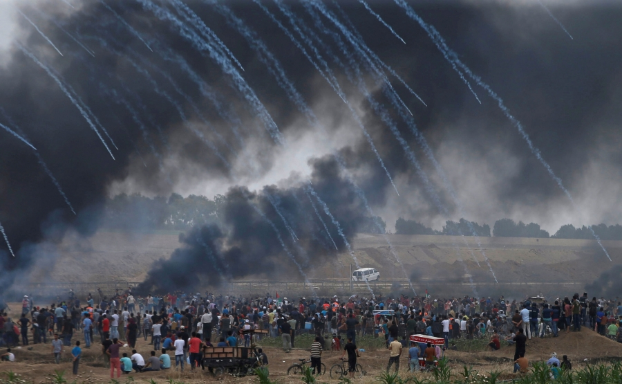 A crowd of people stand in a group. Overhead, gas trails behind tear gas canisters as they're launched into the crowd.