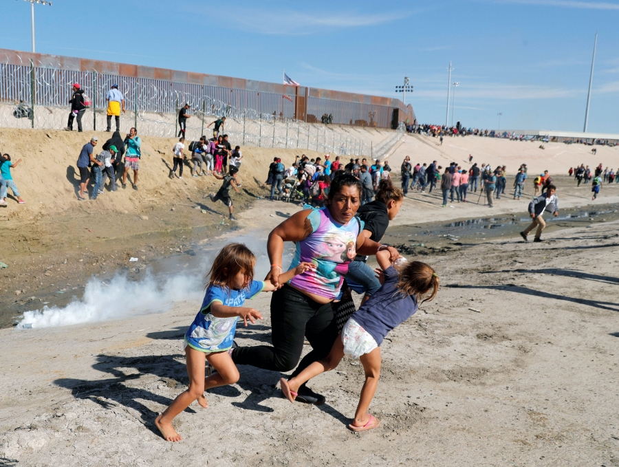 A woman holds the hands of two children as she runs away from the US-Mexico border fence. Behind her are more people running and clouds of tear gas.