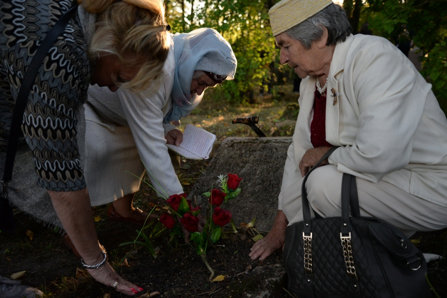 Three women stand around grave, pressing hands into soil