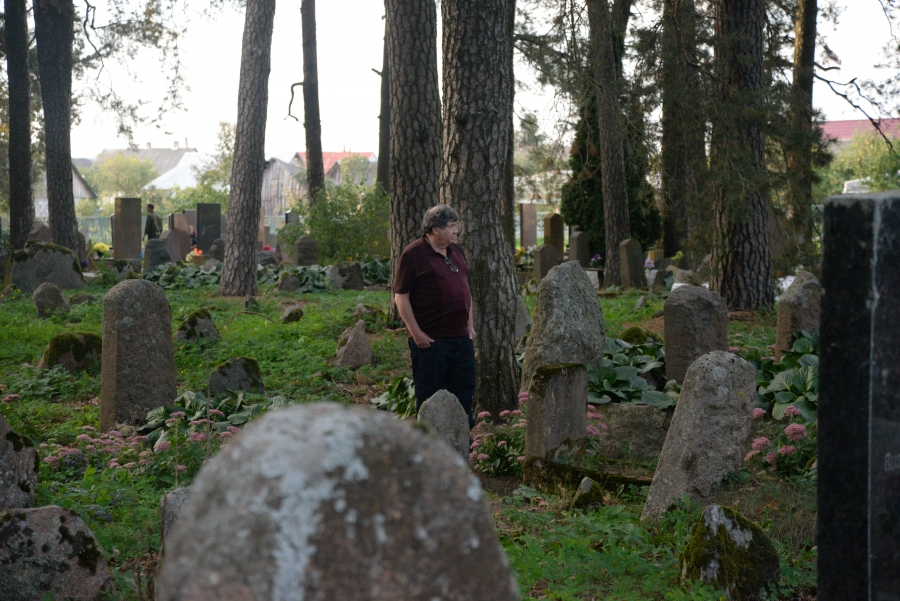 Man standing in lush cemetery