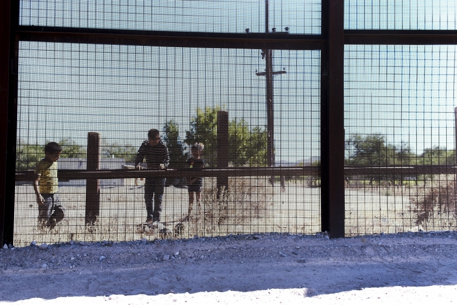 Mesh fencing with children behind, looking onto US side