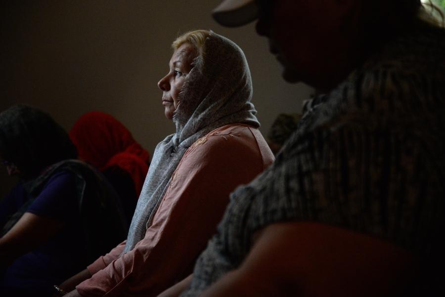 Woman kneeling looking forward, profile view