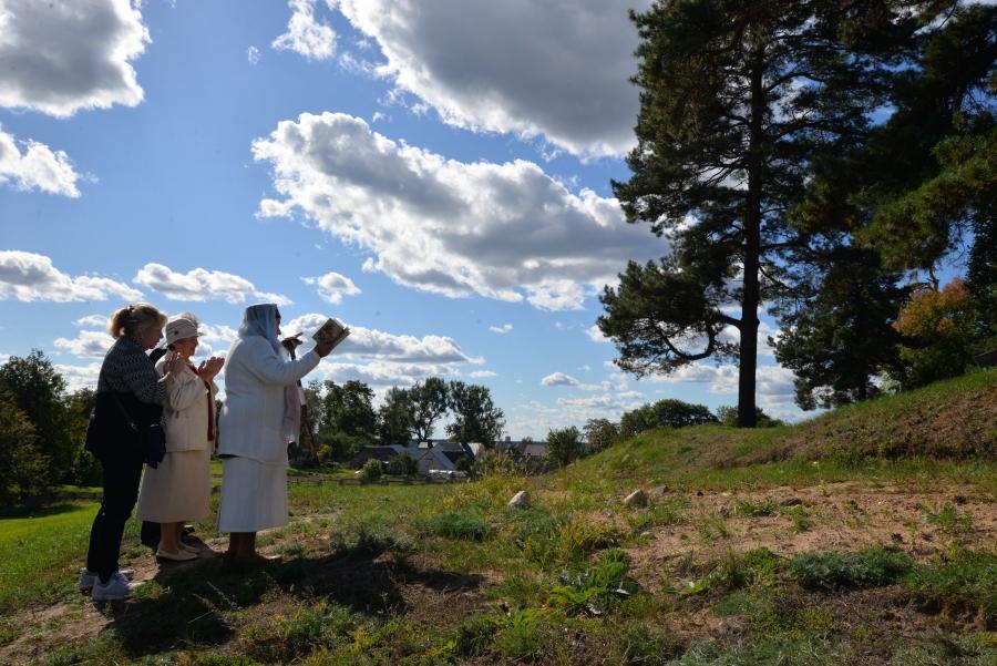 Three women stand green hill, facing gravestone