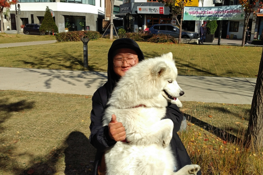 Kim Jong-yoon hugs a white dog.