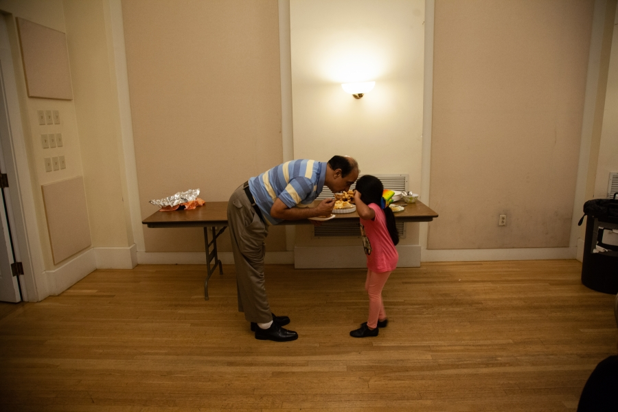 man bending over to meet forehead of young child in hallway