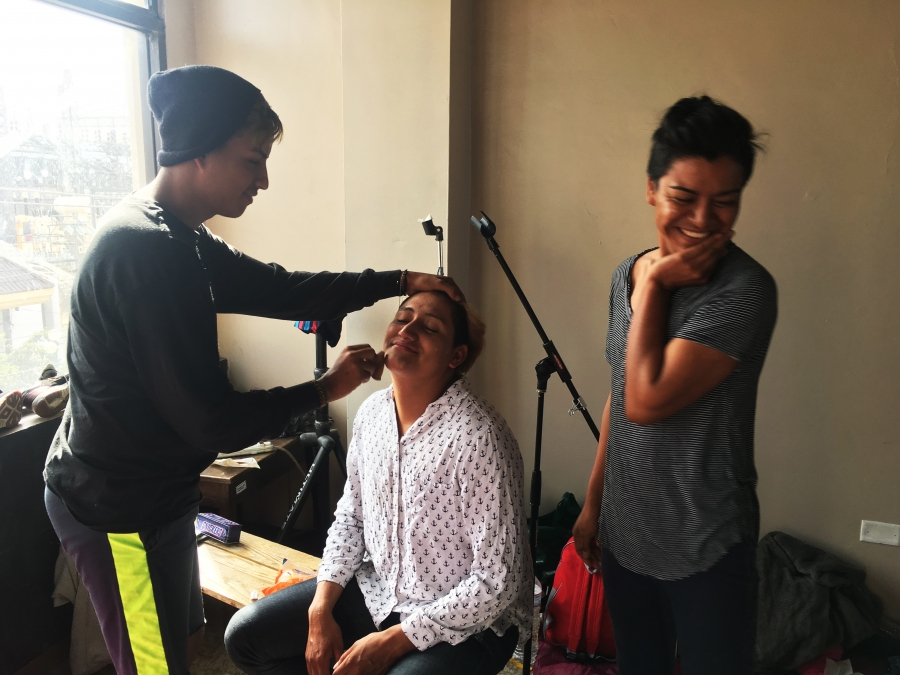 A few migrants prepare for the weddings by putting on makeup. One sits in a chair while another applies makeup and another giggles in the corner