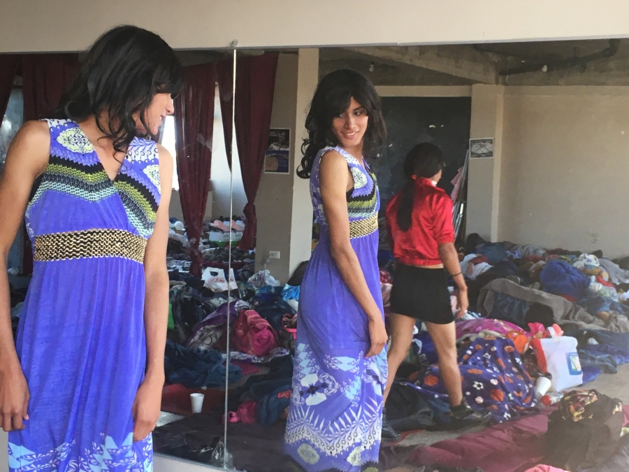a migrant tries on a purple dress and looks in the mirror