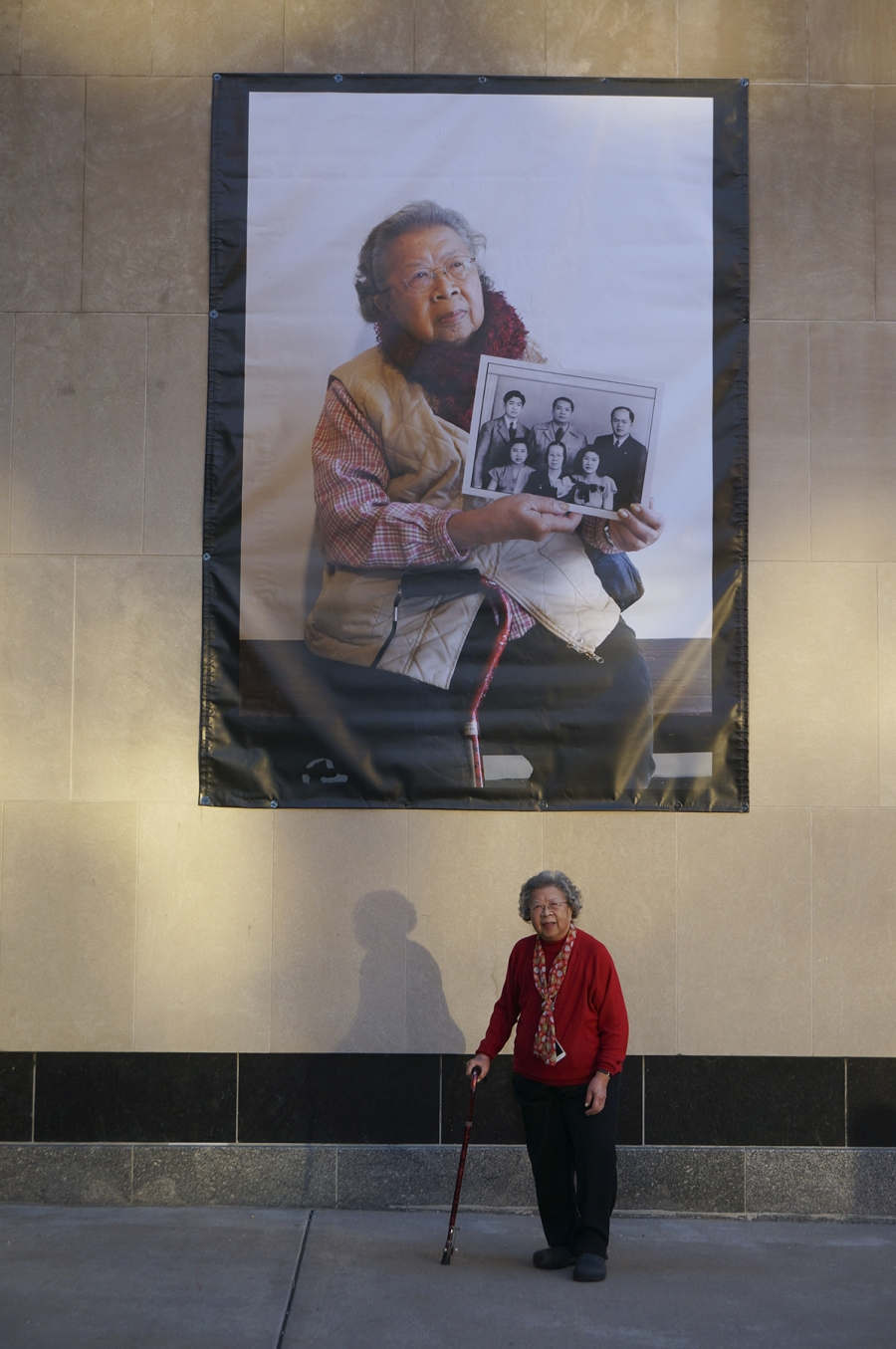 A woman stands in front of her portrait which hangs large on the side of a building