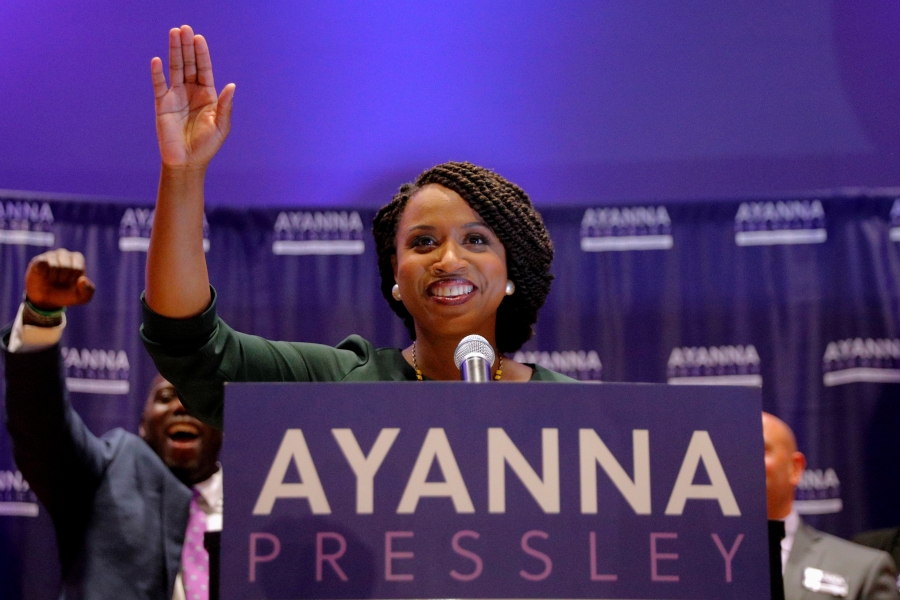 Representative-elect Ayanna Pressley stands behind a podium and waves to the crowd as her husband cheers behind her