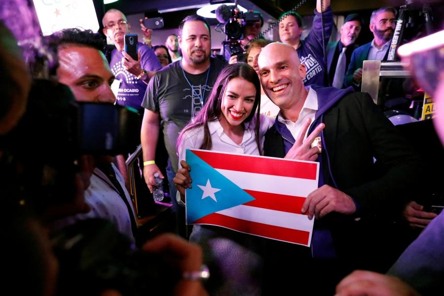 Representative-elect Alexandria Ocasio-Cortez holds a Puerto Rico flag and smiles