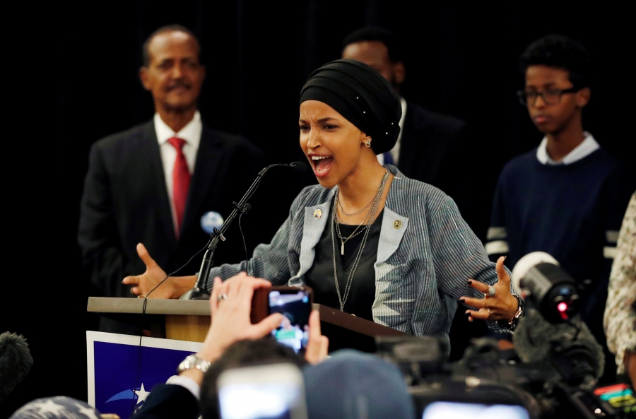 Ilhan Omar speaks at a podium with her arms held out