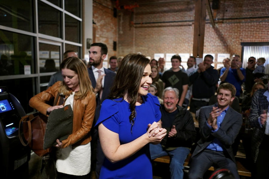 Abby Finkenauer smiles with her hands clasped
