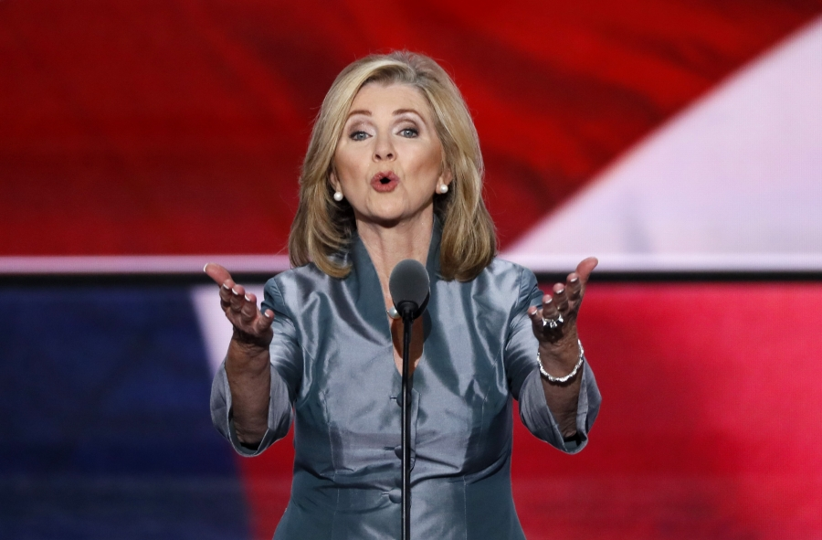 speaks behind a podium with her arms outstretched toward the audience