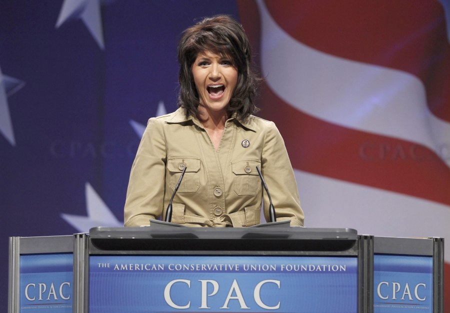 USRepresentative Kristi Noem stands at a podium with an American flag background