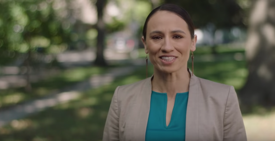 Sharice Davids stands under trees and smiles