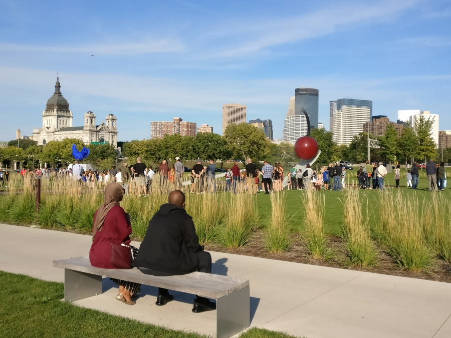 Couple sits on bench facing large statue of cherry in spoon, other milling around on grass