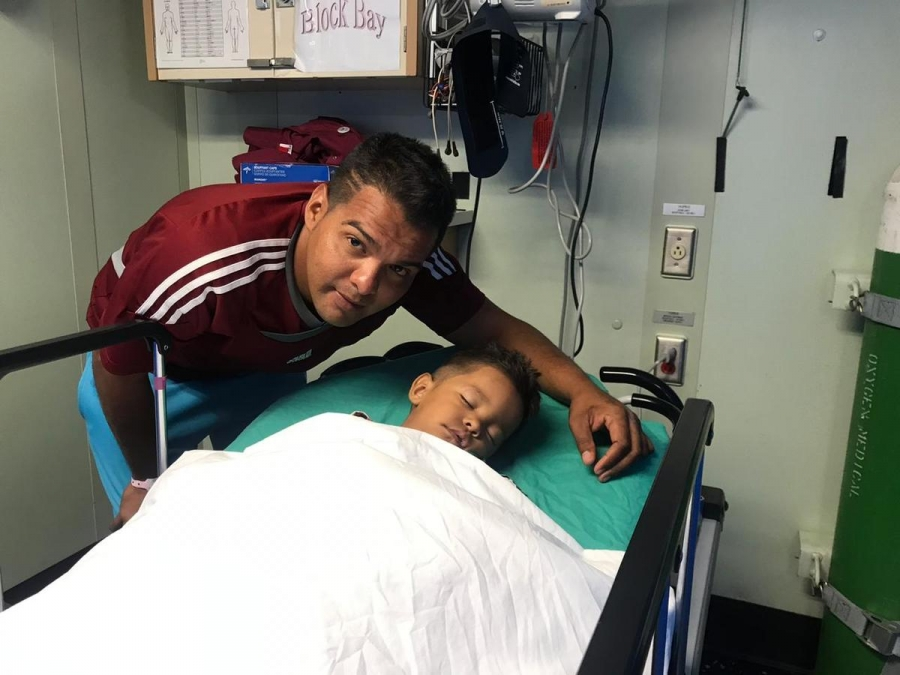 Eduardo Borges crouched over his son who is in a hospital gurney