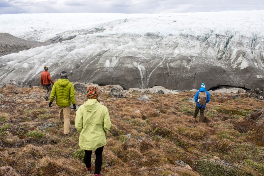 People walk up a hill to the edge of the Greenland ice sheet, which is ice and show as far as the ice can see along the horizon.