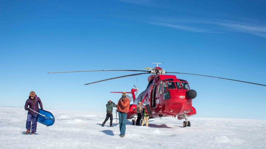 A bright red helicopter lands on the flat ice and snow while people help unload gear from it.