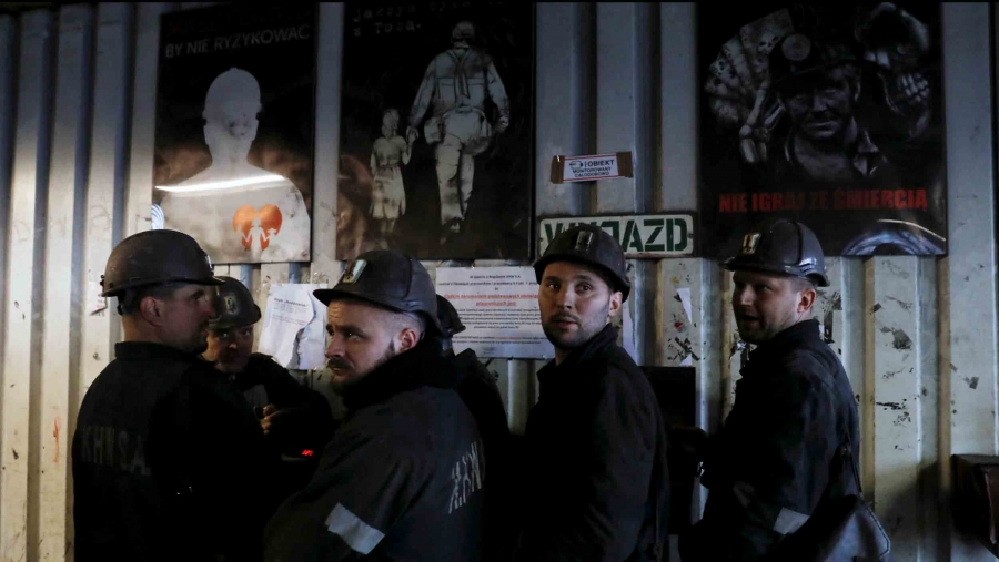 A group of men wearing hard hats and dark grey clothes stand in front of posters depicting miners at work