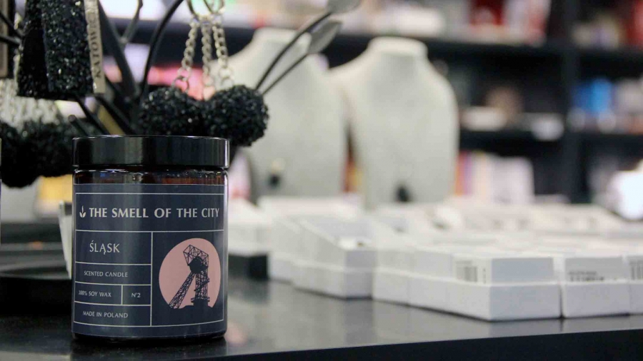 "A candle labeled ""smell of the city"" sits on a counter"