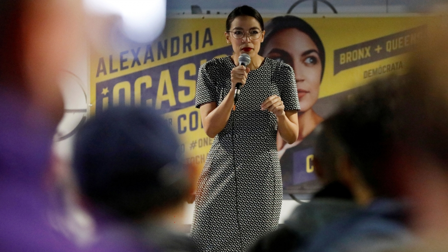 Alexandria Ocasio-Cortez holds a microphone in front of a large campaign banner showing her face