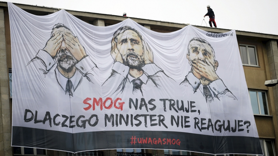 a large banner hangs from a government building with cartoon images of a politician with his eyes, ears and mouth covered.