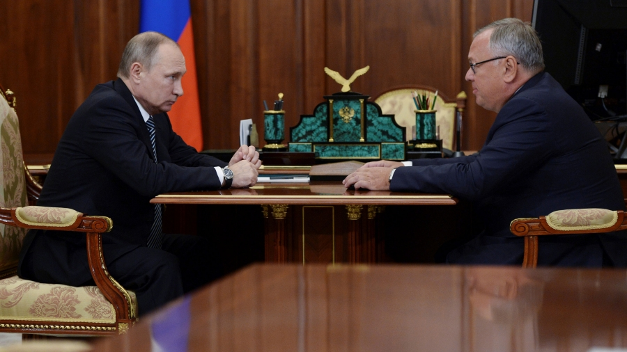 Two men sit with a desk in between them. On the left is Russian President Vladimir Putin.